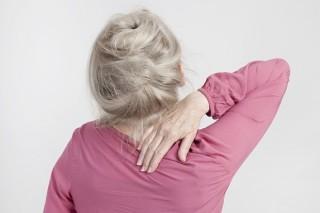 eine ältere blonde Frau hält sich den nacken mit der hand